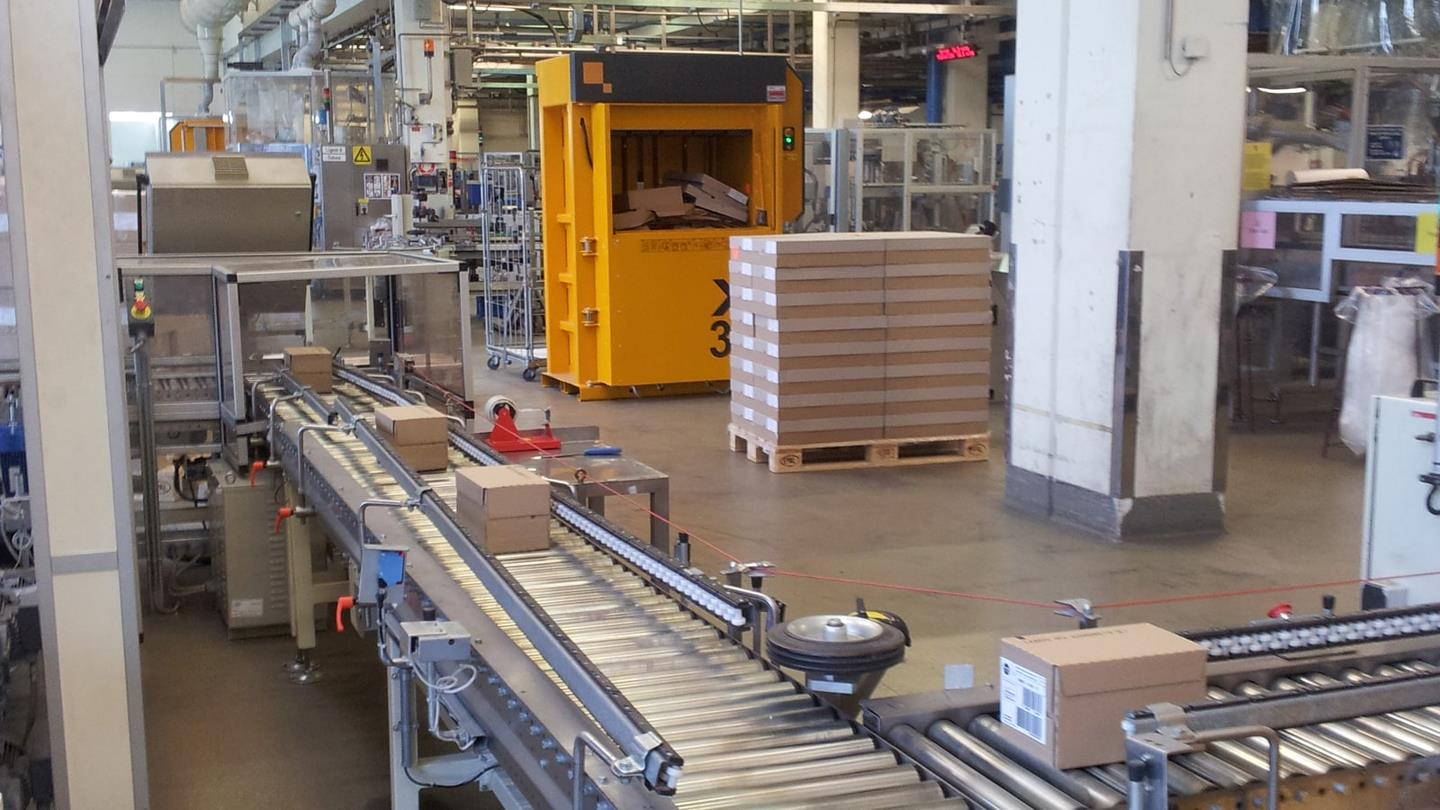 Roller conveyer with cosmetic in boxes next to baler with automatic door