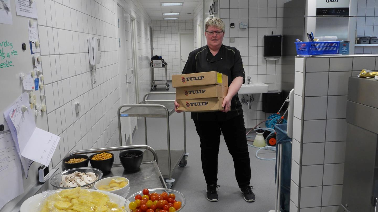 Canteen employee carrying boxes with Tulip meat products