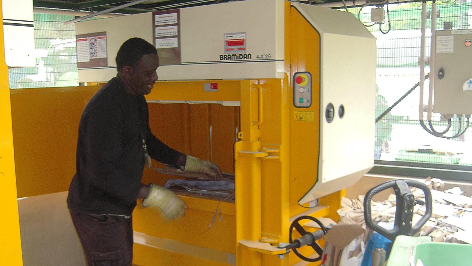 Employee with gloves fills cardboard waste into baler