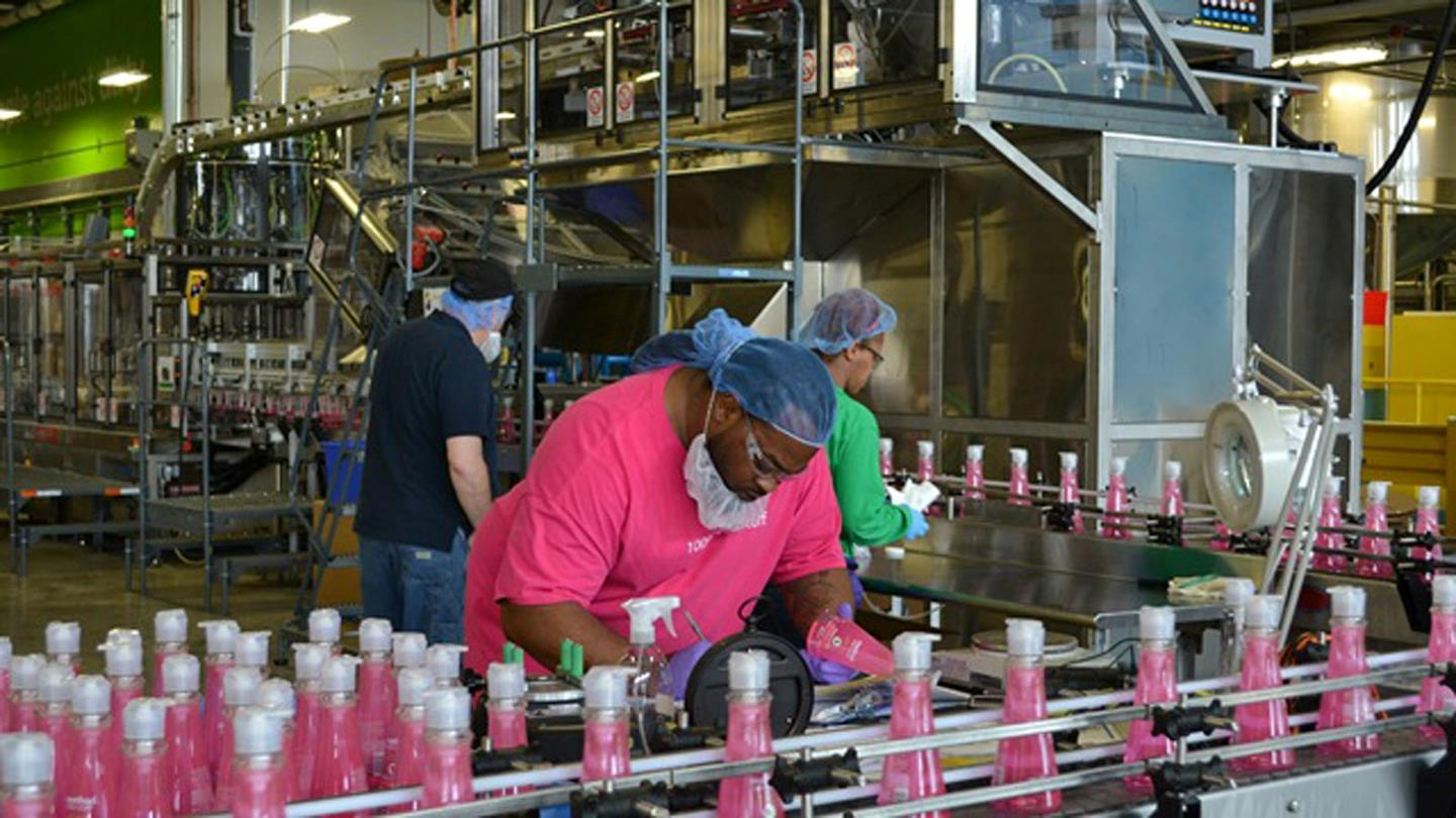 Women with hairnet at assembly line with pink bottles
