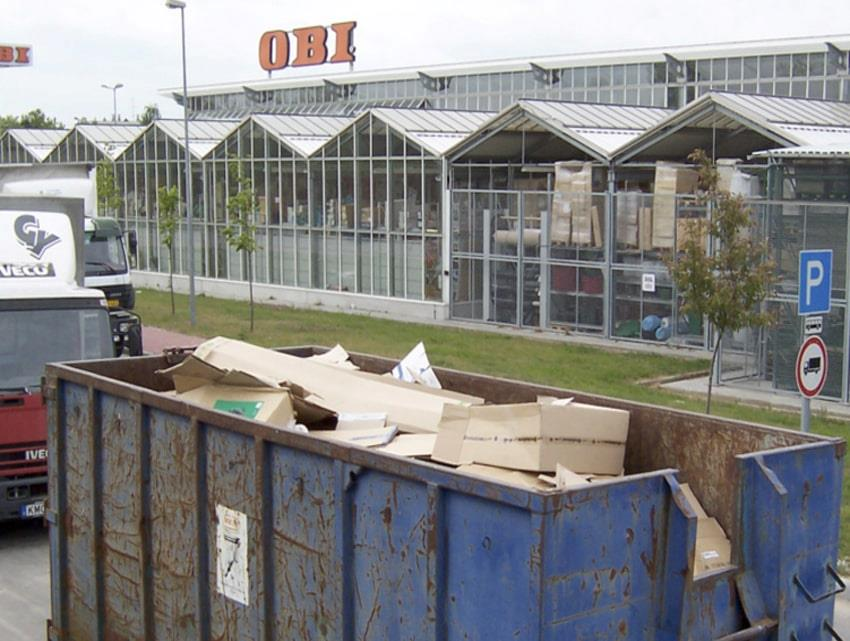 Truck and container with cardboard waste in front of OBI shop