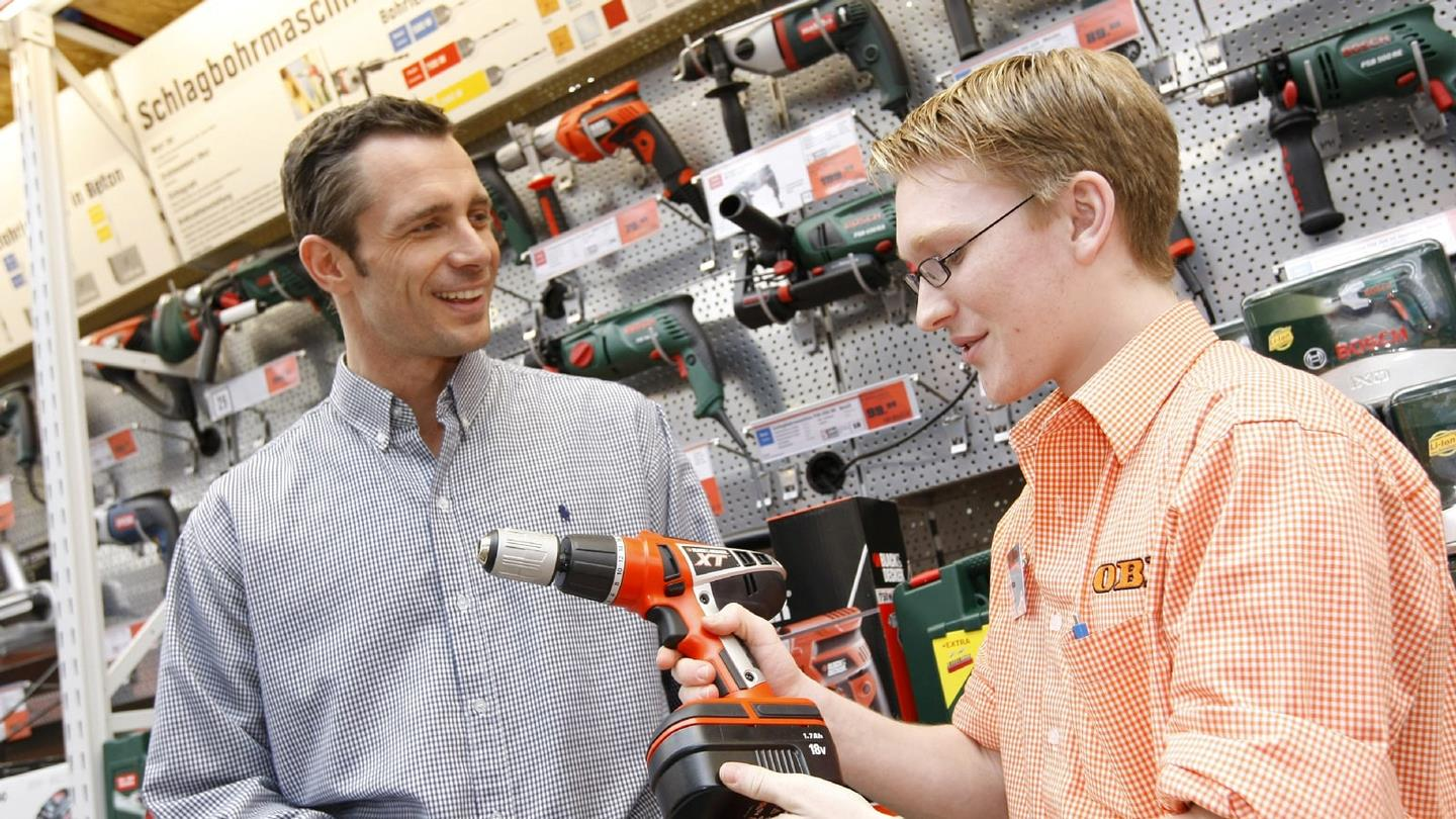 Salesman from OBI DIY centre advises customer with tool purchase