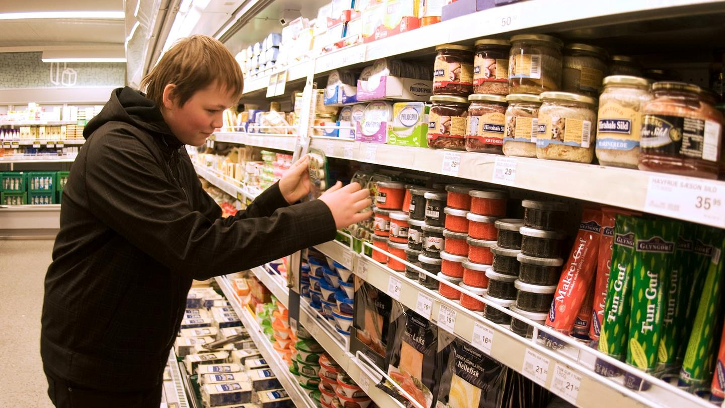 A customer in SuperBrugsen looks for tinned fish products